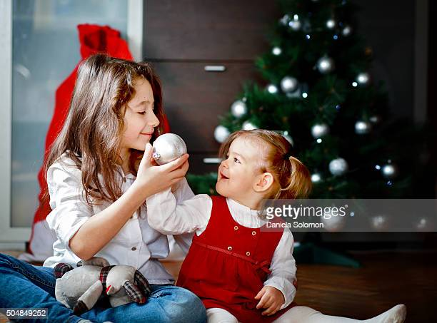 Cute baby girl and her brother sitting on the floor near christmas tree