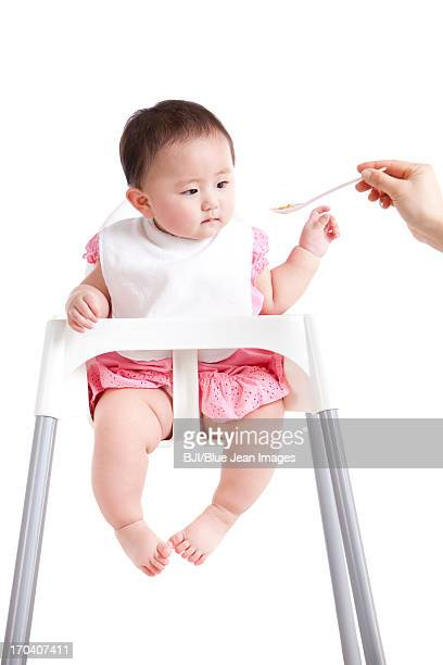 Cute baby girl being fed on baby high chair