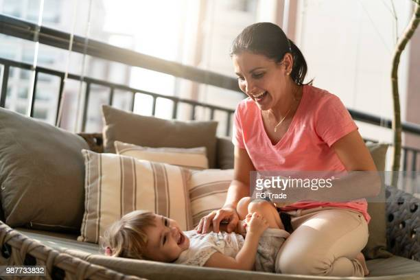 menina bonita se divertindo com sua mãe em casa - fazendo cócegas - fotografias e filmes do acervo