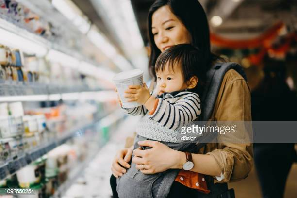 cute baby girl holding a tub of fresh yoghurt while grocery shopping with mother in a supermarket - convenience store stock photos and pictures