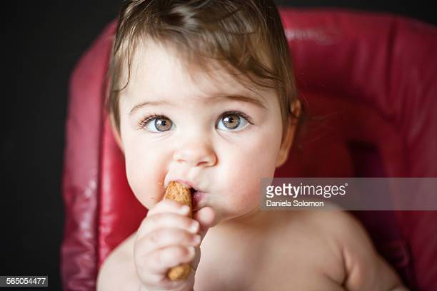 Cute baby girl holding and eating bread