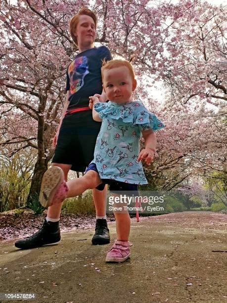 Cute Baby Girl Holding Hands Of Brother While Walking On Footpath