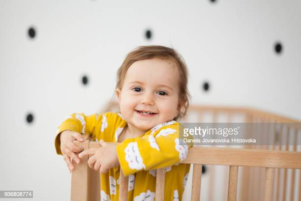 cute baby girl in baby crib - baby girls stock pictures, royalty-free photos & images