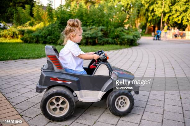 cute baby girl in electric toy car - toy car stock pictures, royalty-free photos & images