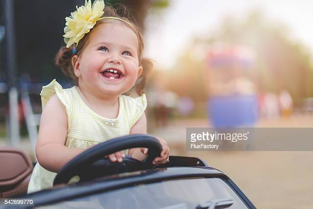 cute baby girl in electric toy car