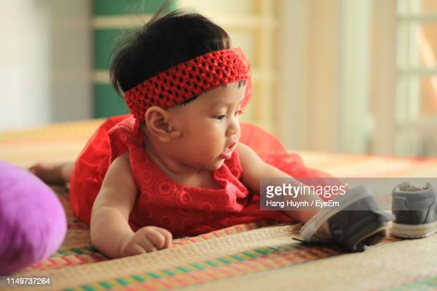5ea63c8d64c Cute Baby Girl In Red Dress Playing With Shoes While Lying On Mat