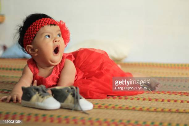 1c480c16212 Cute Baby Girl In Red Dress Yawning While Lying On Mat