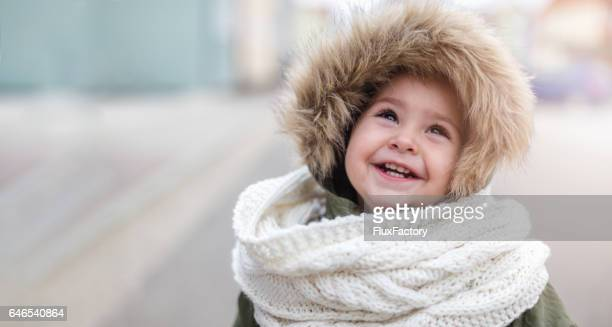 Cute baby girl in winter jacket and scarf looking up