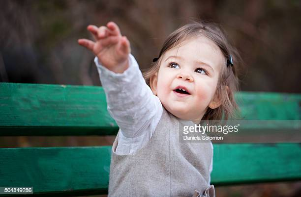 Cute baby girl looking up, hand raised