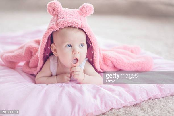 Cute baby girl lying at her stomach covered with jacket