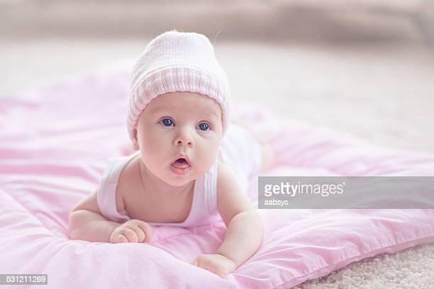Linda niña bebé caer en su estómago mirando hacia arriba