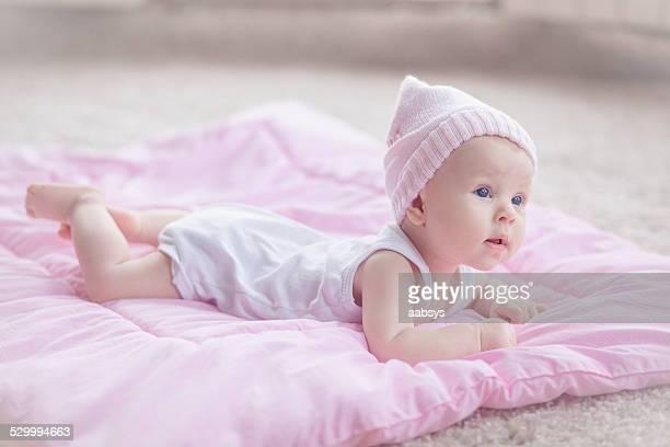 Linda niña bebé caer en su estómago en el piso