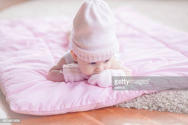 Cute baby girl lying at her stomach playing with mittens