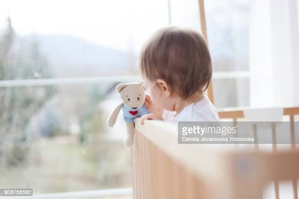cute baby girl playing in baby crib
