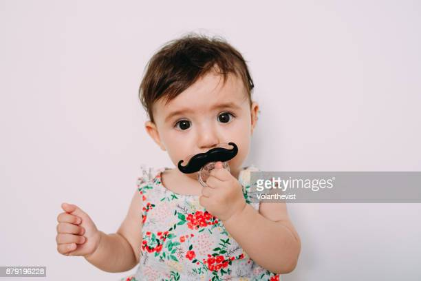 cute baby girl playing with a mustache pacifier - transgender foto e immagini stock