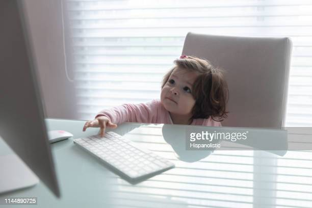 cute baby girl playing with the keyboard and looking at screen - hispanolistic stock photos and pictures