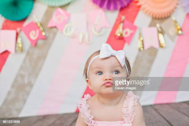 cute baby girl puckering against decoration at her first birthday party - hair bow stock pictures, royalty-free photos & images