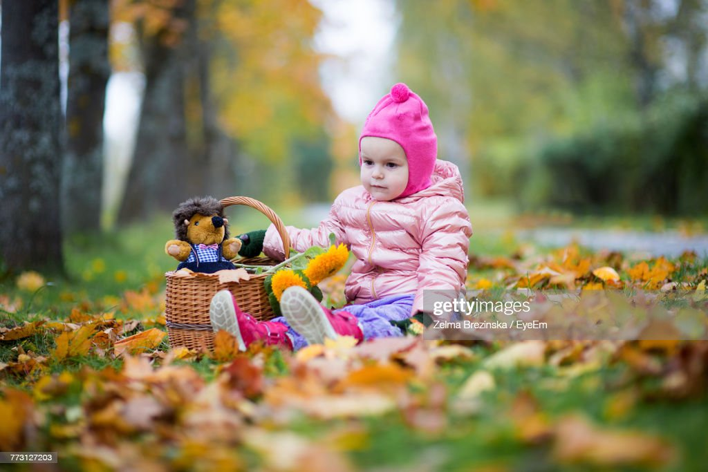 Cute Baby Girl Sitting On Field At Park : Photo