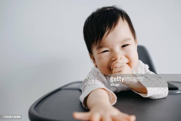 cute baby girl sitting on high chair sucking her thumb and smiling joyfully - chupando dedo - fotografias e filmes do acervo