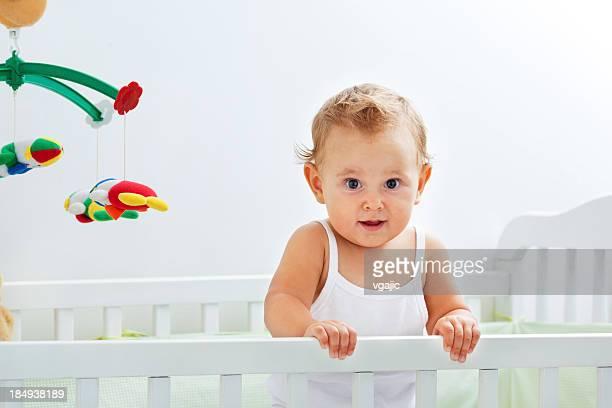 Süßes Baby Mädchen Portrait im Kinderbett Überraschung