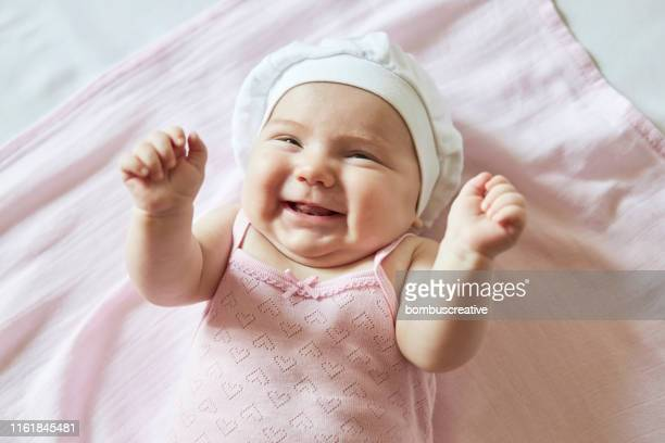 cute baby girl tickling on pink blanket - baby girls stock pictures, royalty-free photos & images