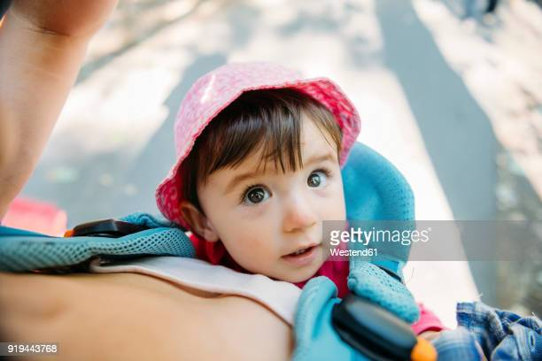 Cute baby girl travelling with mum in a baby carrier