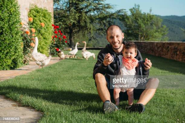 Cute baby girl walking on the grass with the help of her father and geese in the background