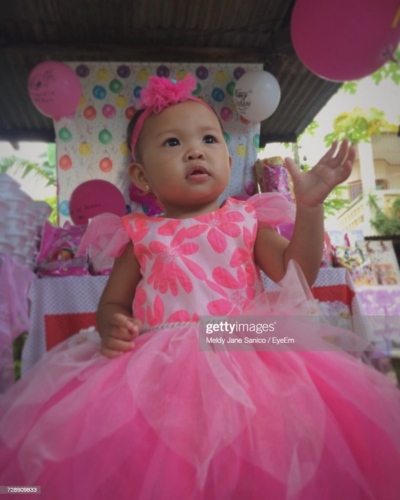cute baby girl wearing pink dress enjoying at birthday party stock