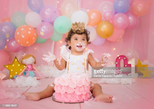 cute baby girl with balloons and birthday cake sitting at home - happybirthdaycrown stock pictures, royalty-free photos & images