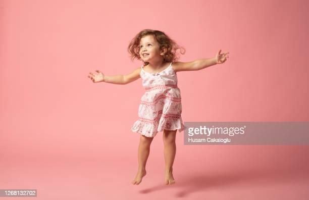 menina bonita com pulando descalço no fundo rosa. - menina - fotografias e filmes do acervo