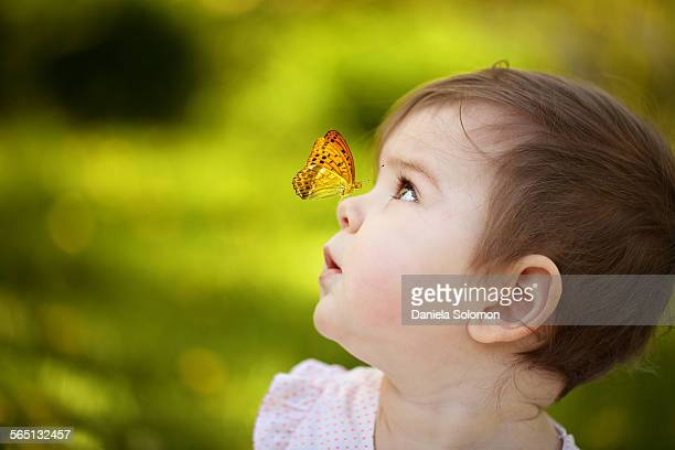 Cute baby girl with butterfly on nose