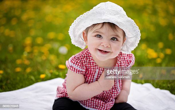 Cute baby girl with hat sitting on the grass