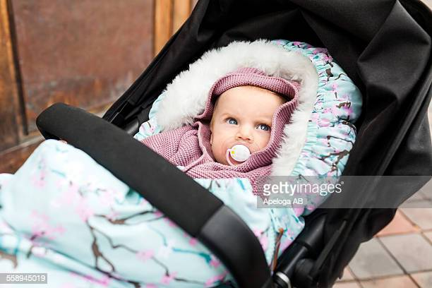 Cute baby girl with pacifier in carriage looking away outdoors