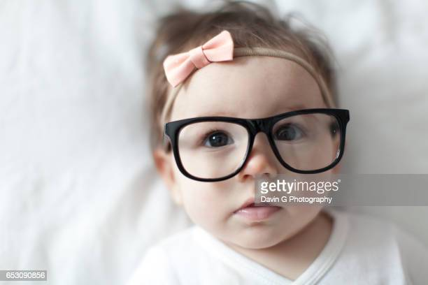 Cute baby girl with pink bow in her hair and wearing dark-frame glasses