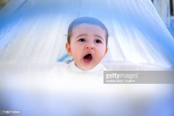 cute baby girl yawning in bed at home - andrea rizzi fotografías e imágenes de stock