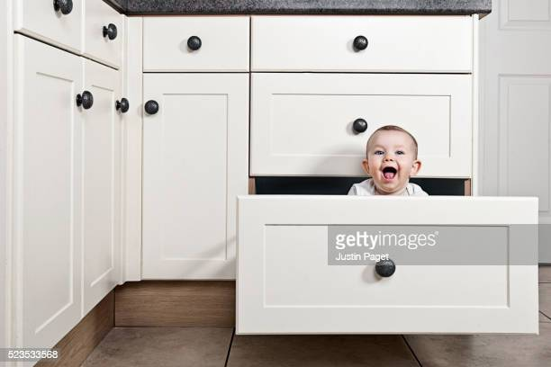 cute baby in kitchen drawer - drawer stock pictures, royalty-free photos & images