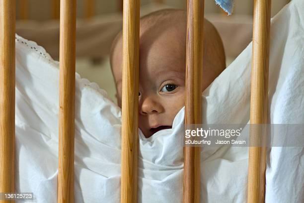 cute baby peeking out from his cot - s0ulsurfing stockfoto's en -beelden