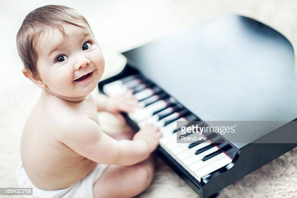 cute baby playing grand piano - grand piano stock photos and pictures