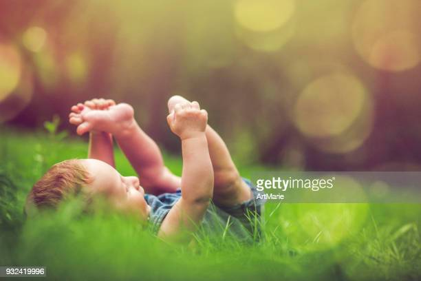 Cute baby playing with his legs on the grass