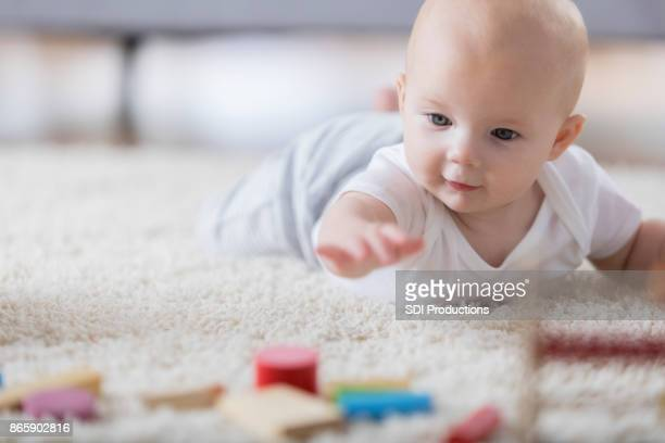 Cute baby reaches for wooden toys on living room rug