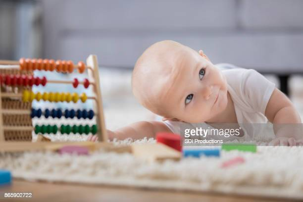 Cute baby seeks encouragement as she tries to reach toys