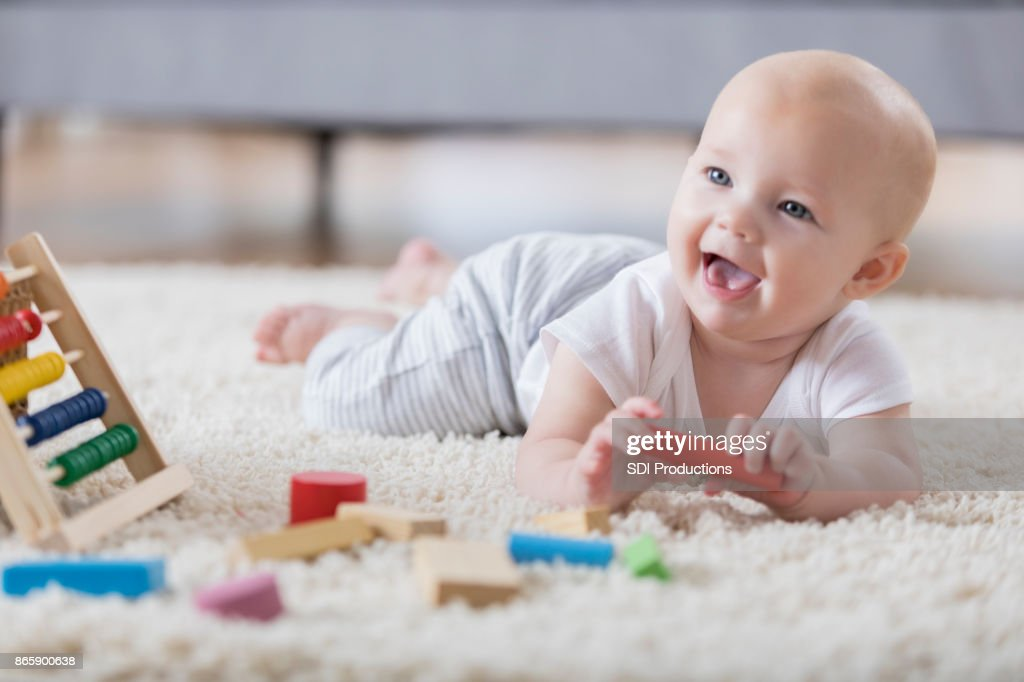 Cute baby sings with open mouth while playing with wooden blocks : Stock Photo