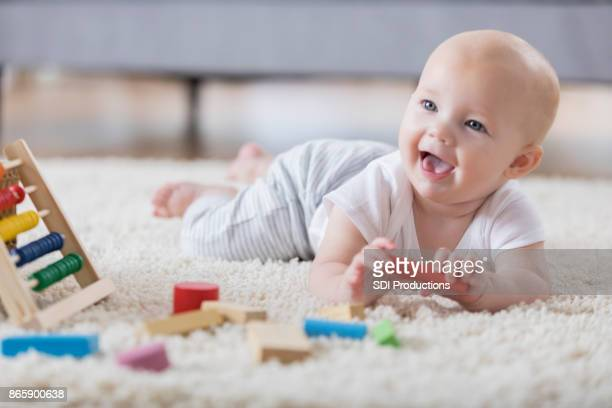 cute baby sings with open mouth while playing with wooden blocks - toy stock pictures, royalty-free photos & images