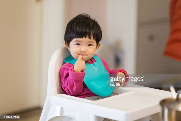 Cute baby Sitting in a high chair waiting for to eat dinner