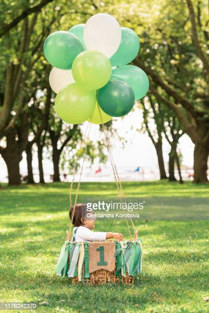 """cute baby sitting in a woven basket with balloons and a green ribbon banner that reads """"one"""". whimsical hot air balloon flight in a beautiful forest clearing. - 1歳以上2歳未満 ストックフォトと画像"""