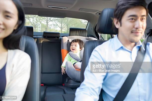 Cute baby sitting in car back seat
