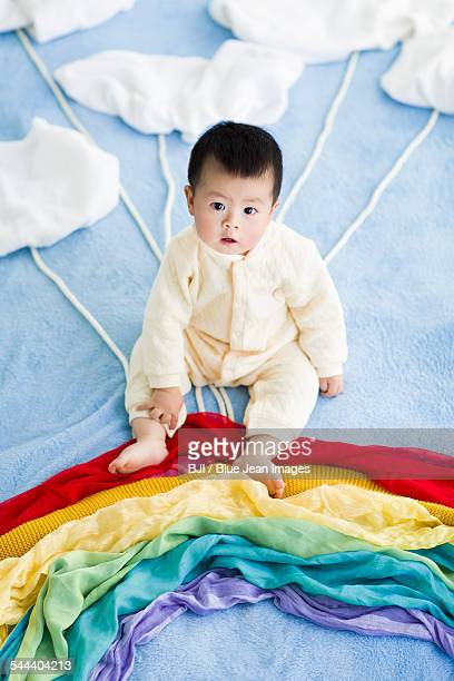 Cute baby sitting on the rainbow