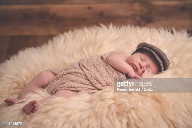 cute baby sleeping on bed - flat cap stock pictures, royalty-free photos & images