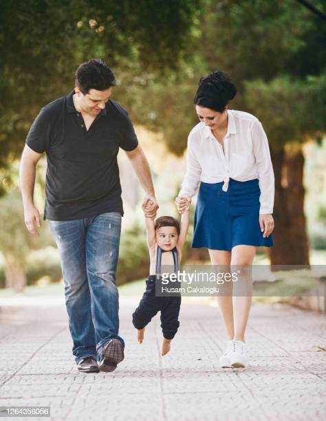 cute baby trying to walk holding the hands of his parents in the park - turkey middle east stock pictures, royalty-free photos & images