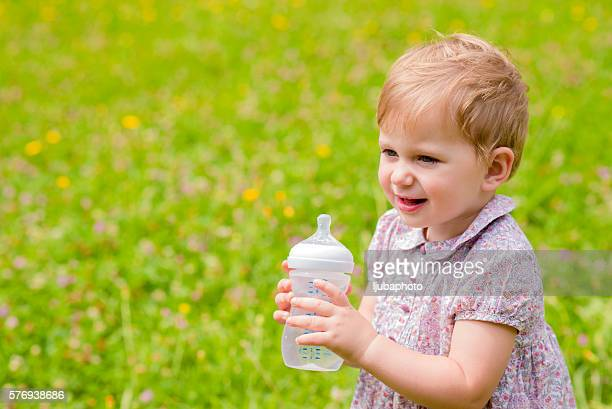 Cute baby with a bottle in nature
